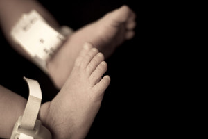 Closeup of a baby newborn infants feet and toes in sepia tone.  Shallow depth of field.