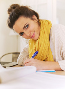 Closeup of a beautiful smiling woman looking at camera while writing on her notepad