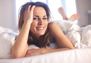 Closeup of a casual woman in a bright bedroom lying on bed