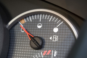 Closeup of a gas gage displaying that the car has an empty tank.  Shallow depth of field.