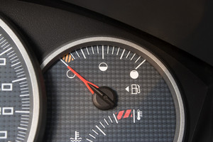 Closeup of a gas gage displaying that the car is running on empty.