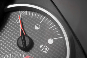 Closeup of a gas gage from a car.  It has selective color and the needle is pointing to empty.