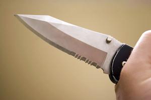 Closeup of a hand gripping a dangerous knife with a sharp blade.