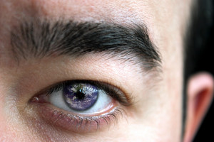 Closeup of a mans eye and eyebrow with the earth superimposed in his iris.
