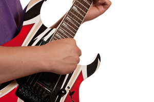 Closeup of a mans hands strumming an electric guitar isolated over a white background.