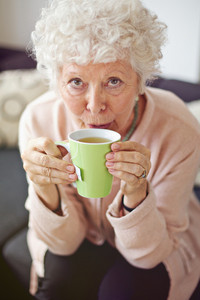 Closeup of a mature lady looking at you while drinking her tea