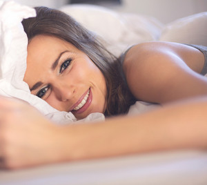 Closeup of a relaxed woman lying on bed smiling