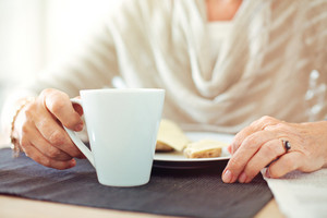 Closeup of a senior woman's hands with a cup of coffee