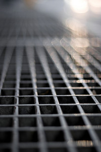Closeup of a sidewalk subway grate with shallow depth of field.