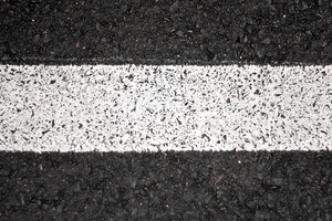 Closeup of a tar or asphalt pavement texture with a white line painted down the center.
