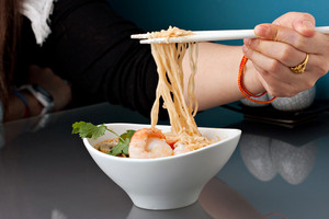 Closeup of a woman eating shrimp and Thai noodles from a bowl with chopsticks.