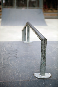 Closeup of a worn skate park grind rail with copy space.  Shallow depth of field.