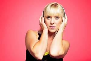 Closeup of a young blonde girl holding the headphone on her head
