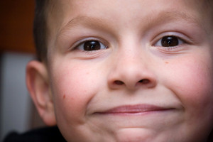 Closeup of a young boy who is smiling happily. Shallow depth of field.