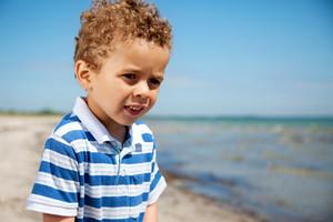Closeup of an adorable boy spending summer on a sunny beach