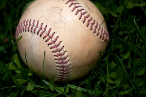 Closeup of an aged and worn hardball or baseball laying in the green grass. Shallow depth of field.