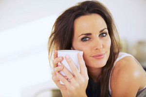 Closeup of an attractive woman holding a mug close to her face