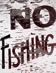 Closeup of an old vintage sign by a lake that reads NO FISHING.