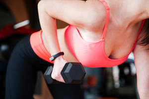 Closeup of attractive young sportswoman standing and working out with dumbbells in gym