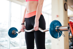 Closeup of barbell holded by young sportswoman working out in gym