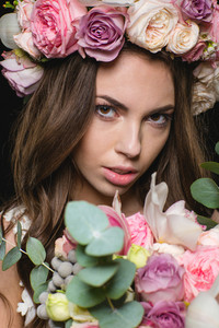 Closeup of beautiful young female in wreath of roses with bouquet of flowers over black background