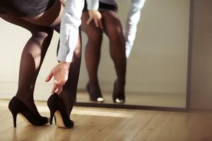 Closeup of female legs wearing high heels shoes. Woman adjusting high heels in front of mirror.