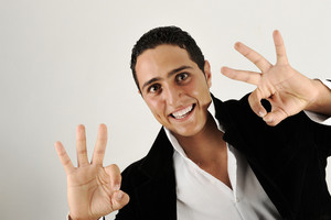 Closeup of good looking young man gesturing okay sign over white background