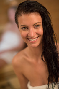 Closeup of happy young woman with wet hair in sauna