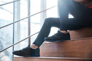 Closeup of legs in black leggings and sneakers of young sportswoman sitting on stairs