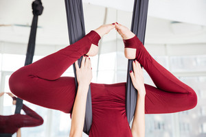 Closeup of legs of sportswoman doing aerial yoga exercise in studio