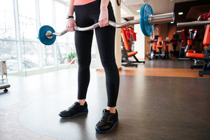 Closeup of legs of young woman athlete standing and exercising with barbell in gym