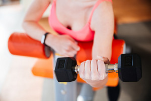 Closeup of metal dumbbell holded by young woman athlete in pink top training in gym