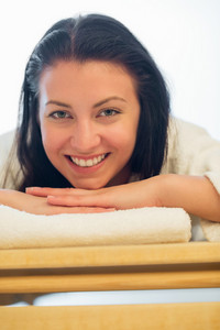Closeup of smiling woman resting on bed at beauty spa