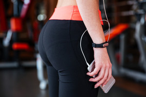 Closeup of sportswoman with fitness tracker on her hand standing and holding cell phone in gym