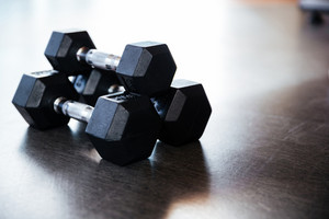 Closeup of three metal dumbbells on the floor in gym