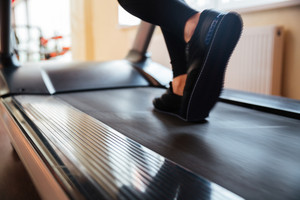 Closeup of treadmill used by sportswoman in black sneakers for running in gym