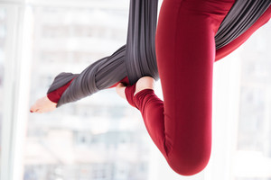 Closeup of young woman legs using hammock and doing aerial yoga exercises