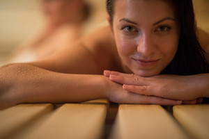 Closeup of young woman lying on wooden bench at sauna