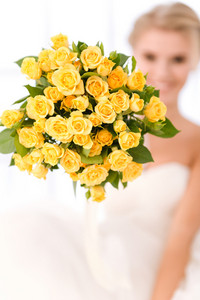 Closeup portrait of a bride holding flowers. Focus on flowers