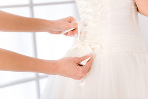 Closeup portrait of a bride putting white wedding dress