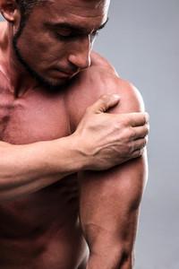 Closeup portrait of a handsome man touching his shoulder