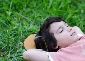 Closeup portrait of a little happy boy sleeping on grass in nature and dreaming