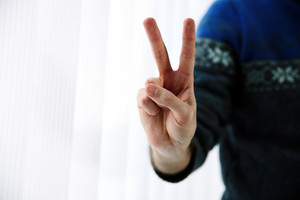 Closeup portrait of a male hand with two fingers up in the peace or victory symbol