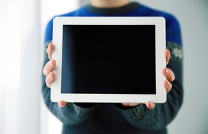 Closeup portrait of a male hands showing tablet computer screen
