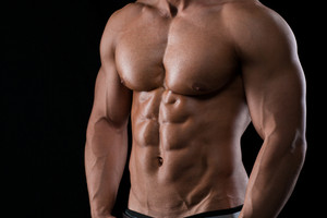 Closeup portrait of a muscular male chest on black background