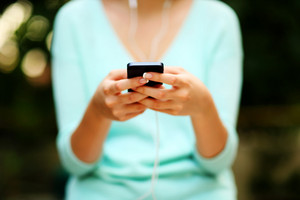Closeup portrait of a woman using smartphone with headphones