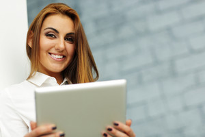 Closeup portrait of a young businesswoman with tablet computer