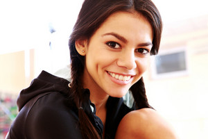 Closeup portrait of a young smiling fit woman at gym