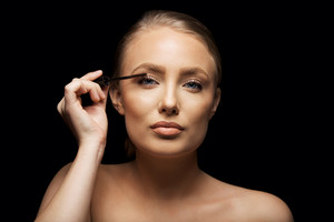 Closeup portrait of attractive young woman putting some mascara onto her eyelashes with make up brush. Beautiful caucasian female model against black background.