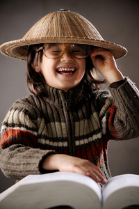 Closeup portrait of cute kid wearing chinese hat reading book